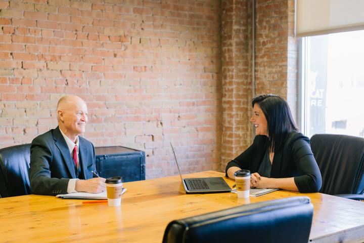 man and woman talking inside office