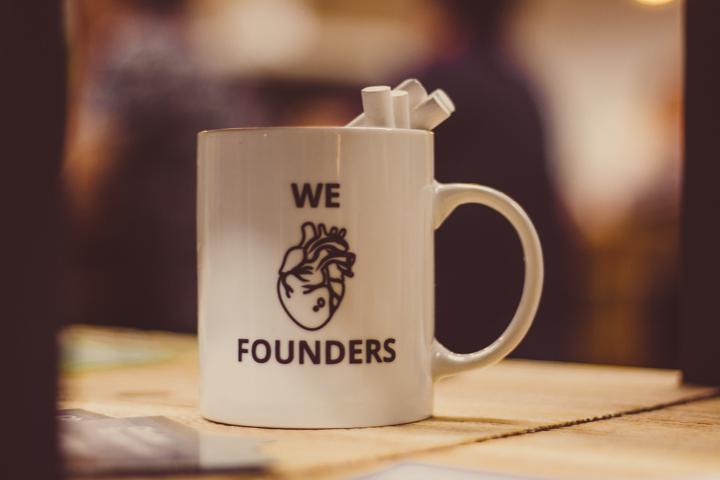 selective focus photo of we Founders heart-printed ceramic mug