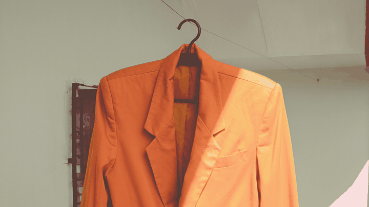 Orange blazer on a hanger in Anchor Group colors