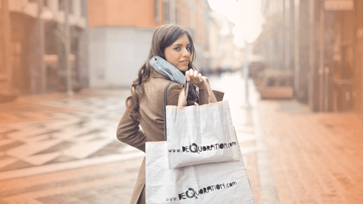 woman holding two shopping bags looking over her shoulder smiling