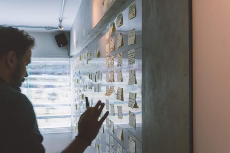 NetSuite Demand Planning male putting sticky notes on wall