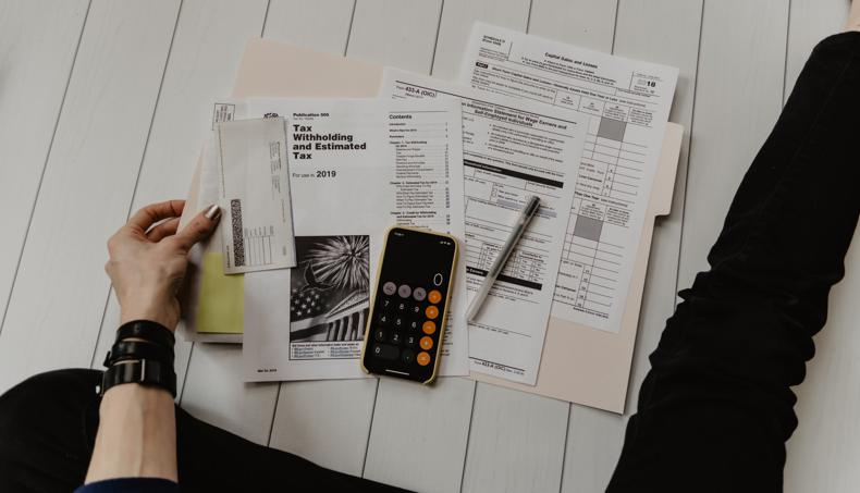 NetSuite Multi-Book Accounting person holding paper near pen and calculator