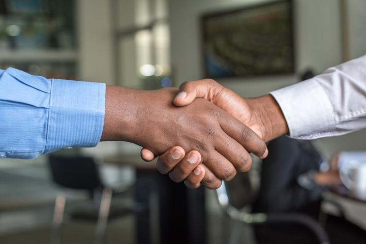 netsuite two people shaking hands blog