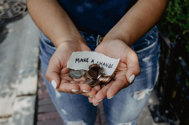 NetSuite for Nonprofit Organizations person showing both hands with make a change note and coins