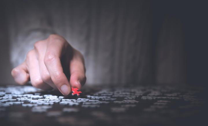 man holding red puzzle piece around gray puzzle pieces
