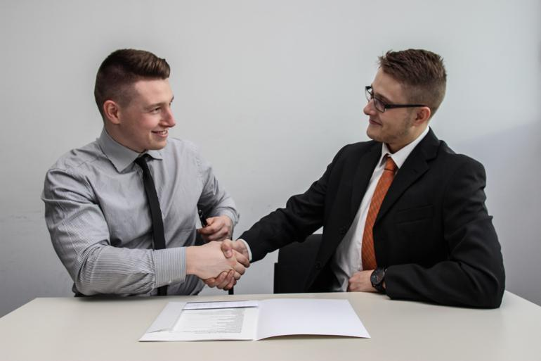 NetSuite CRM two men facing each other while shake hands and smiling