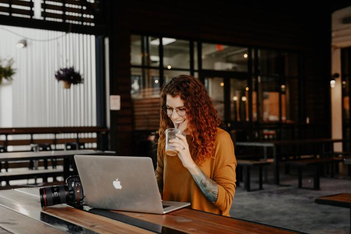 woman in orange long sleeve shirt sitting in front of silver macbook blog