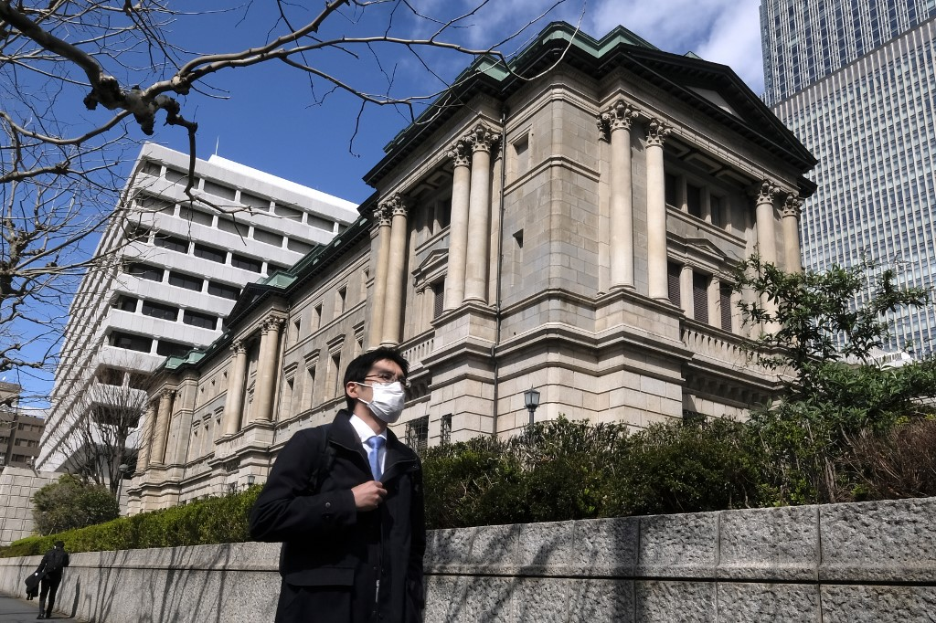 Japan boosts easing measures, cuts growth forecast