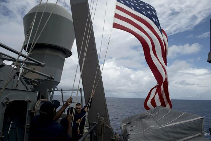 US Navy personnel pull down an American flag during a maritime exercise on the USS John S McCain in the South China Sea near waters claimed by Beijing in a file photo. Photo: AFP/Noel Celis
