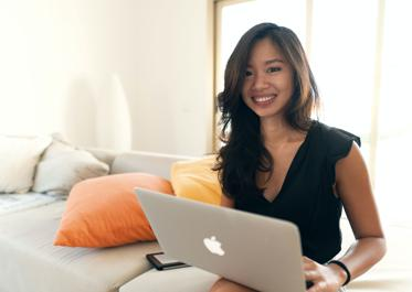 woman in black long sleeve shirt sitting on bed using macbook