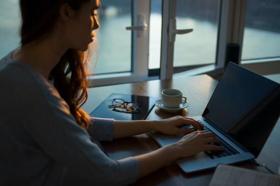 woman sitting beside table using laptop evening