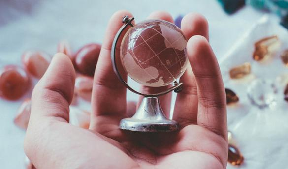 person holding gray metal framed desk globe paper weight
