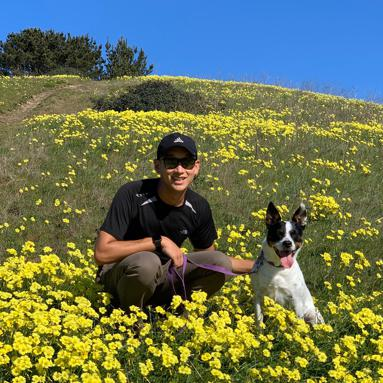 Alex with a dog in the flowers