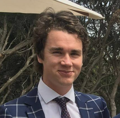 a boy in a suit with curly hair