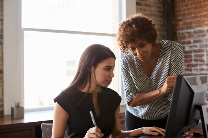Woman mentoring coworker in front of computer screen