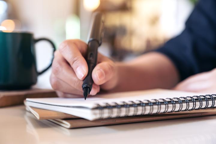 Photo of person writing plans in a notebook