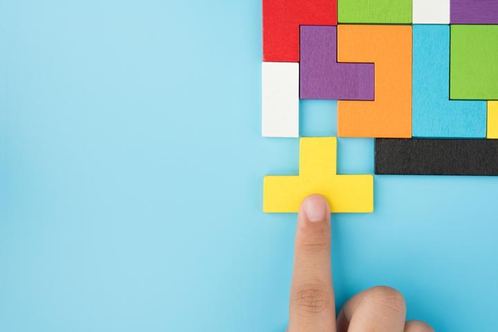 Photo of hand completing puzzle