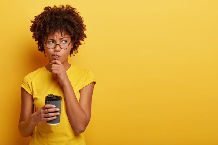 Woman in yellow contemplating over yellow background