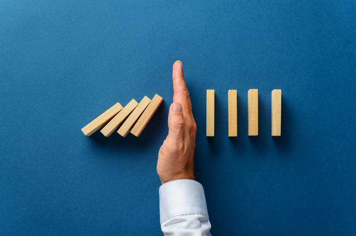 Photo of hand stopping the tumbling of dominoes; example of business crisis management recovery