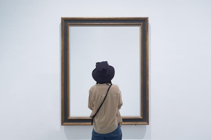 Photo of woman looking at empty visual on gallery wall