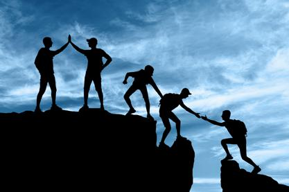 Team of mountain climbers reaching summit