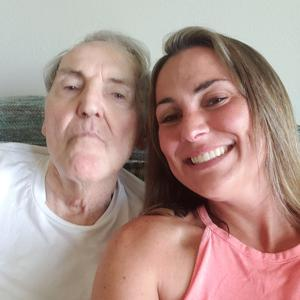Caregiver taking a smiling selfie with her father