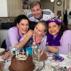 two sister caregivers with their mother having a party and smiling