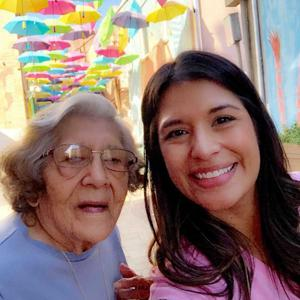 Caregiver taking a smiling selfie with her grandmother and colourful umbrellas in the background