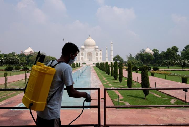 FILE PHOTO: A man sanitizes railings in the premises of Taj Mahal after authorities reopened the monument to visitors, amidst the coronavirus disease (COVID-19) outbreak, in Agra, India, September 21, 2020. REUTERS/Alasdair Pal/File Photo