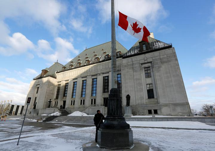 FILE PHOTO: A worker raises a Canadian flag in front of the Supreme Court building in Ottawa March 21, 2014. REUTERS/Chris Wattie/File Photo