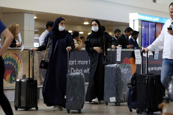 FILE PHOTO: Travellers wear masks as they arrive at the Dubai International Airport, after the UAE's Ministry of Health and Community Prevention confirmed the country's first case of coronavirus, in Dubai, United Arab Emirates January 29, 2020. REUTERS/Christopher Pike