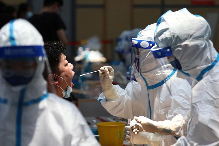 FILE PHOTO: A medical worker in protective suit collects a swab from a resident for nucleic acid testing at a sports centre in Jiangning district, following new cases of the coronavirus disease (COVID-19) in Nanjing, Jiangsu province, China July 21, 2021. cnsphoto via REUTERS