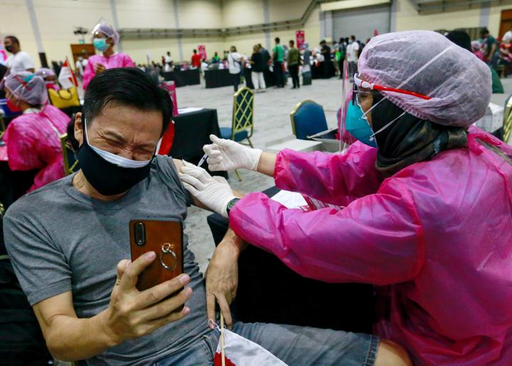 FILE PHOTO: A man wearing a protective face mask reacts as he receives a dose of a vaccine against the coronavirus disease (COVID-19) during a mass vaccination program at the Jakarta Convention Center building in Jakarta, Indonesia, July 31, 2021. REUTERS/Ajeng Dinar Ulfiana