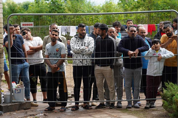 Migrants gather near a fence at a temporary detention center in Kazitiskis, Lithuania, August 12, 2021. REUTERS/Janis Laizans