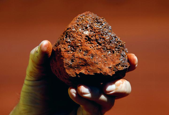 FILE PHOTO: A miner holds a lump of iron ore at a mine located in the Pilbara region of Western Australia, December 2, 2013. REUTERS/David Gray