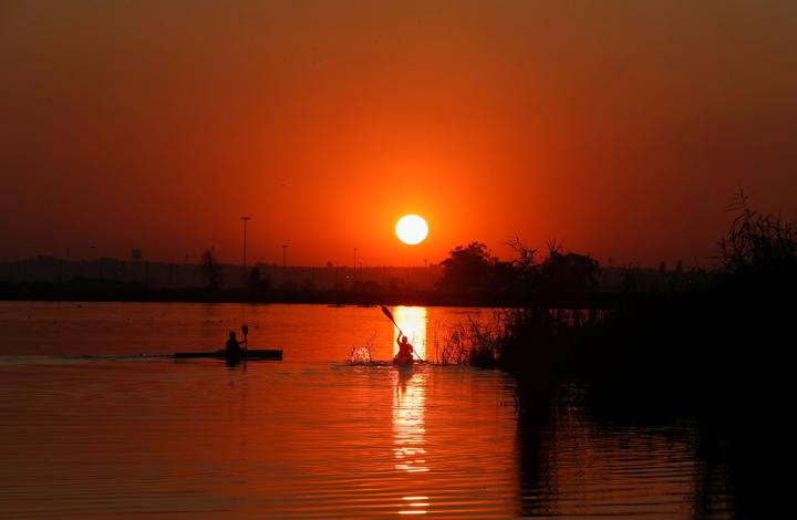 Canoeists are seen during training as the sun sets at the Orlando Dam in Soweto, South Africa, June 21, 2021. REUTERS/Siphiwe Sibeko