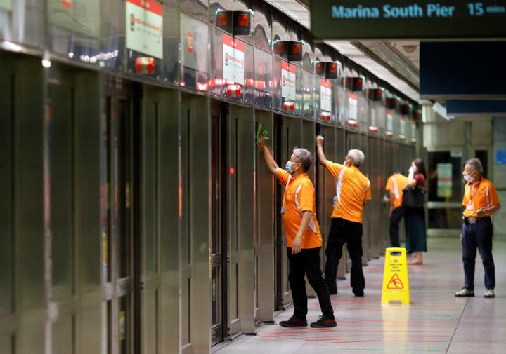 FILE PHOTO: Workers wipe down doors at a train station during the coronavirus disease (COVID-19) outbreak in Singapore August 17, 2020. REUTERS/Edgar Su/File Photo