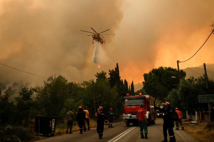 A firefighting helicopter makes a water drop as a wildfire burns in the village of Vilia, Greece, August 18, 2021. REUTERS/Alkis Konstantinidis