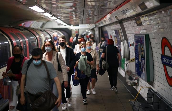 People, some wearing protective face masks, walk along a platform at Oxford Circus underground station, amid the coronavirus disease (COVID-19) pandemic, in London, Britain, July 4, 2021. REUTERS/Henry Nicholls/Files
