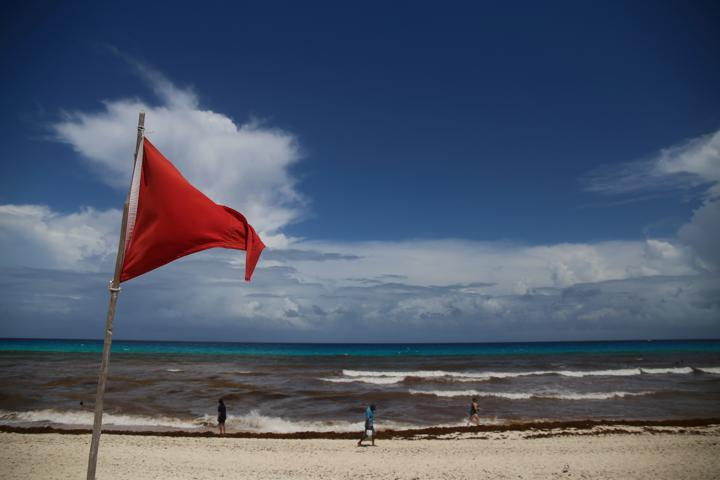 FILE PHOTO: A red flag on the beach warns beachgoers of hazards due to the proximity of Hurricane Grace in Cancun, Mexico August 18, 2021. REUTERS/Paola Chiomante NO RESALES. NO ARCHIVES