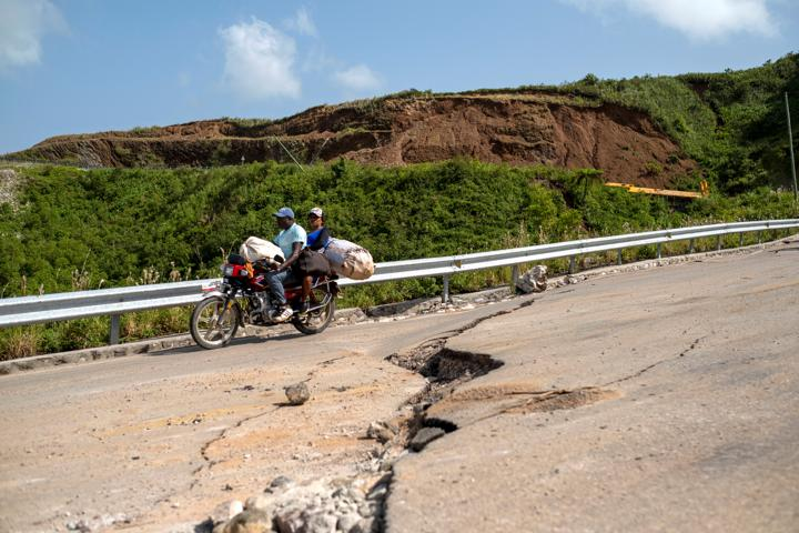 A motorcycle drives on a road with cracks caused by a 7.2 magnitude quake in Marceline, Haiti August 22, 2021. REUTERS/Ricardo Arduengo