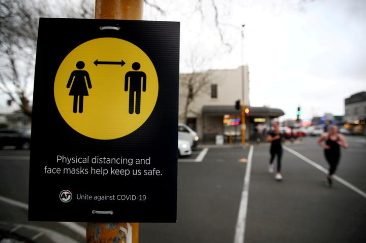 FILE PHOTO: People jog past a social distancing sign on the first day of New Zealand's new coronavirus disease (COVID-19) safety measure that mandates wearing of a mask on public transport, in Auckland, New Zealand, August 31, 2020. REUTERS/Fiona Goodall/File Photo