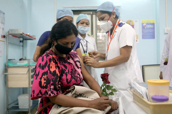 FILE PHOTO: A healthcare worker holding a rose is vaccinated against COVID-19 at a medical centre in Mumbai, India, January 16, 2021. REUTERS/Francis Mascarenhas/File Photo