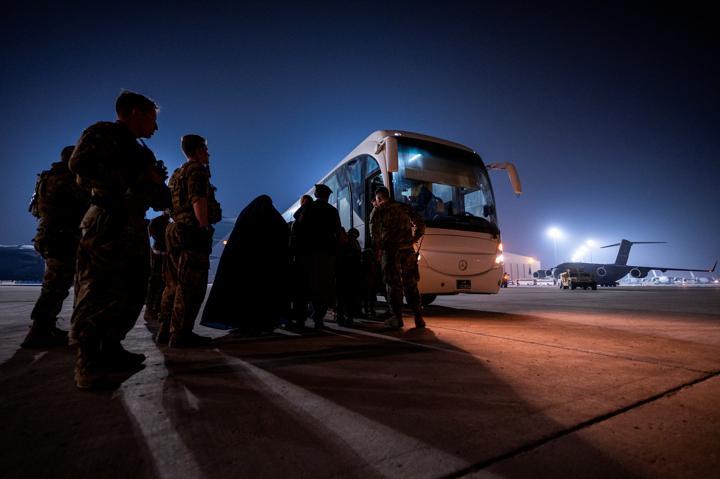 FILE PHOTO: Airman assist Afghan evacuees onto a shuttle, August 23, 2021, at Al Udeid Air Base, Qatar. Picture taken August 23, 2021. U.S. Air Force/Senior Airman Noah D. Coger/Handout via REUTERS/Files