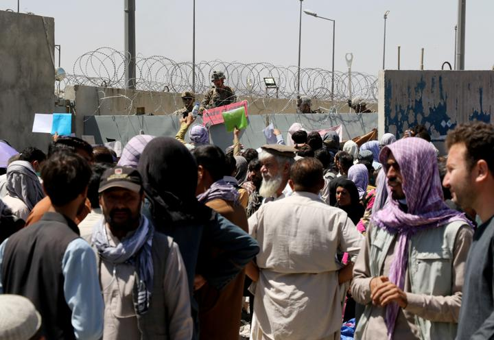 Crowds of people show their documents to U.S. troops outside the airport in Kabul, Afghanistan August 26, 2021. REUTERS/Stringer
