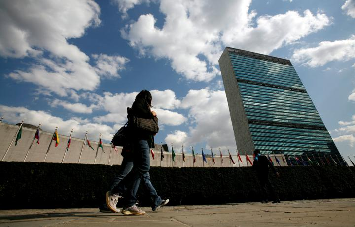 FILE PHOTO: Tourists walk past the United Nations Headquarters in New York, March 24, 2008. At left is the U.N. General Assembly building and at right is the U.N. Secretariat building. REUTERS/Mike Segar