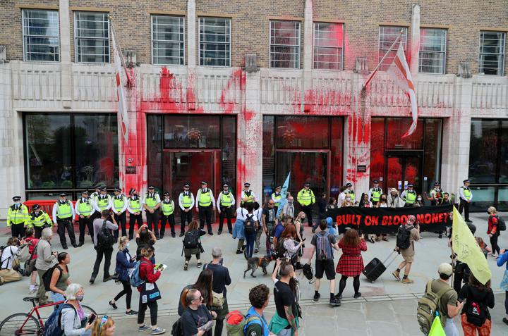 Police officers stand in front of a bulding stained with red paint during an Extinction Rebellion protest, in London, Britain August 27, 2021. REUTERS/May James