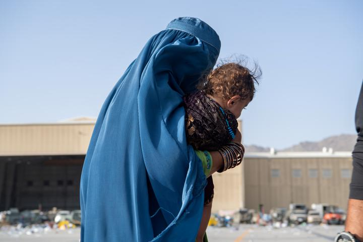 FILE PHOTO: A woman carries a child as passengers board a U.S. Air Force C-17 Globemaster III assigned to the 816th Expeditionary Airlift Squadron in support of the Afghanistan evacuation at Hamid Karzai International Airport in Kabul, Afghanistan, August 24, 2021. U.S. Air Force/Master Sgt. Donald R. Allen/Handout via REUTERS