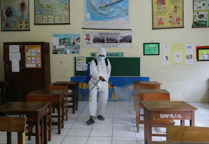 An employee wearing personal protective equipment (PPE) sprays disinfectant after a class as schools reopen on a trial basis after the government extended restrictions to curb the spread of coronavirus disease (COVID-19) in Jakarta, Indonesia, August 30, 2021. REUTERS/Ajeng Dinar Ulfiana