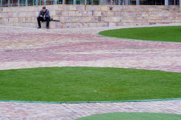 FILE PHOTO: A lone man sits at a deserted Federation Square on the first day of a lockdown, as the state of Victoria looks to curb the spread of a coronavirus disease (COVID-19) outbreak in Melbourne, Australia, July 16, 2021. REUTERS/Sandra Sanders